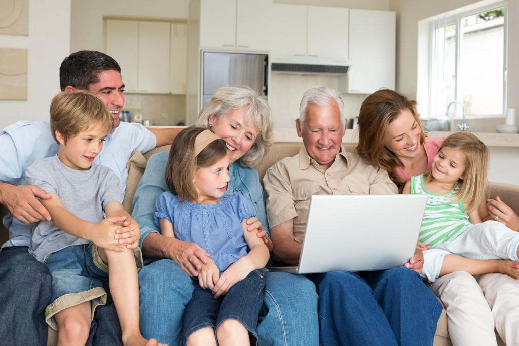 Smiling multigeneration family using laptop in living room