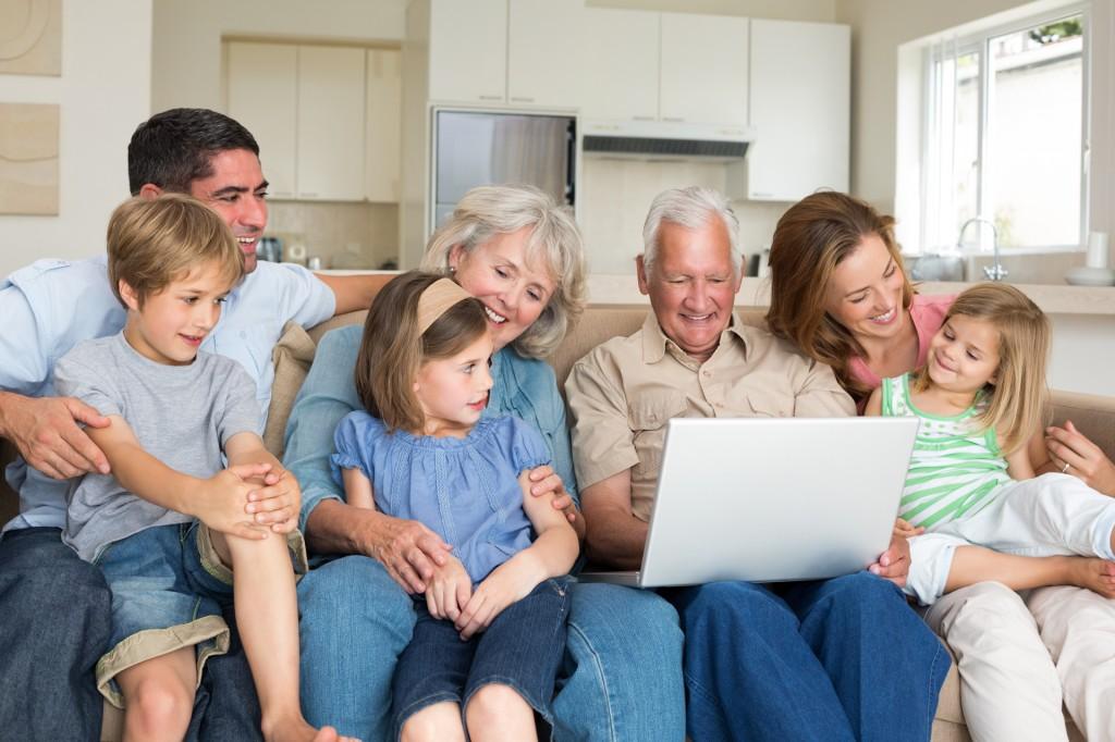 Smiling multigeneration family using laptop in living room